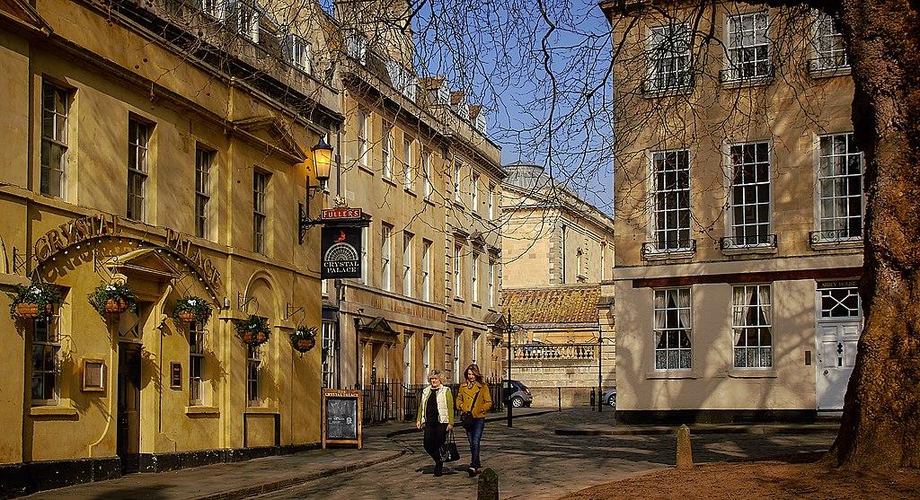 Prédios de cores amarelo e bege em Bath, com duas mulheres andando na rua