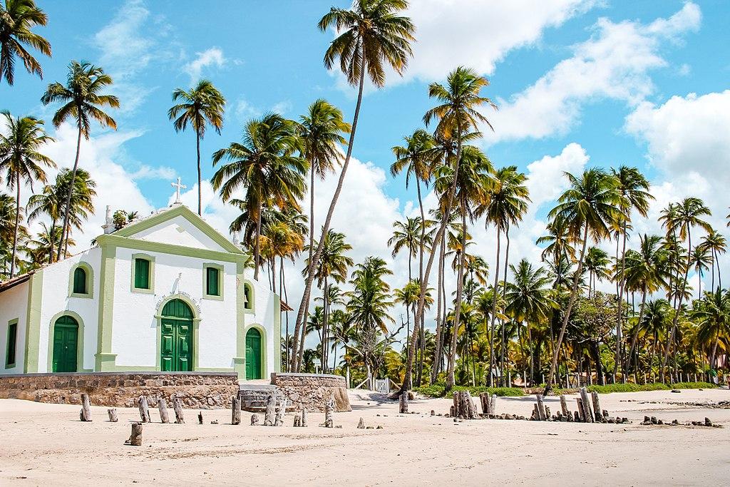 Foto de palmeiras, capela e céu azul com poucas nuvens em Pernambuco, na Praia dos Carneiros