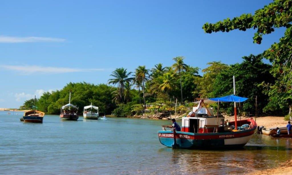 Praia tranquila em Caraíva, com barco na beira-mar