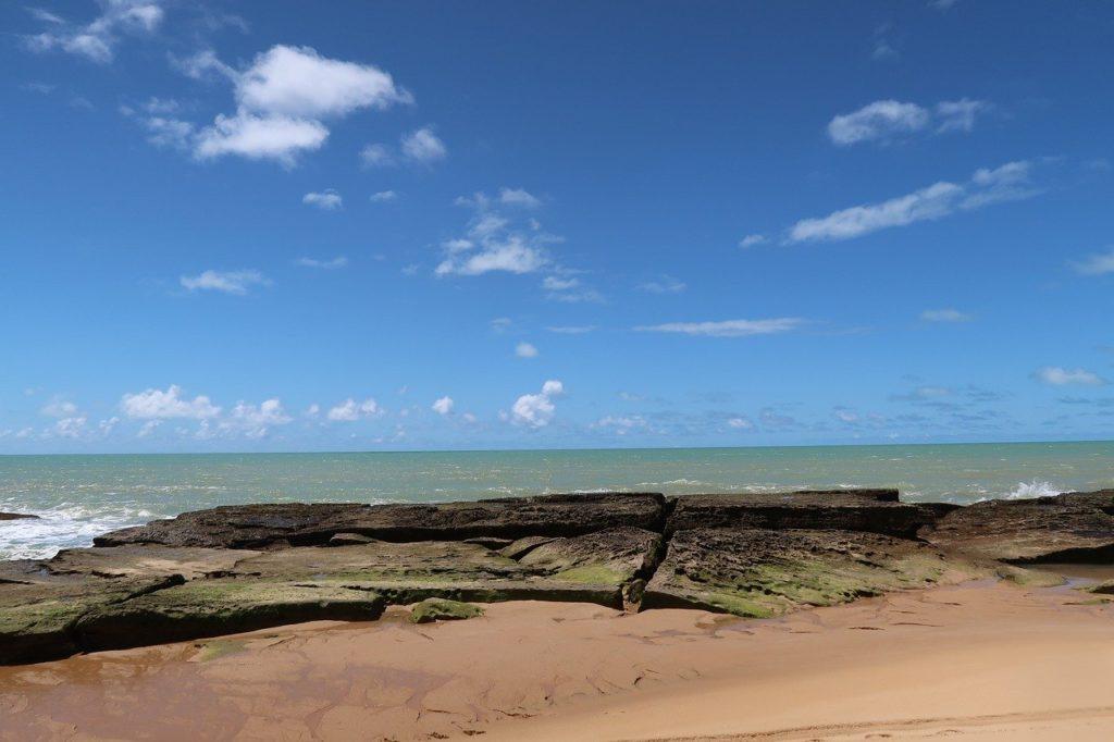 Foto de praia em Caraíva, na Bahia, com mar claro e céu azul