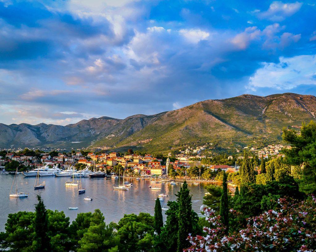 Paisagem de cidade croata, com montanhas ao fundo, casas na encosta, barcos no porto, e vegetação em primeiro plano