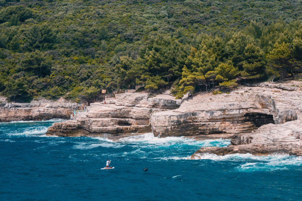 Costa de pedras, com floresta ao fundo, do Mar Adriático na Croácia, com mar azul profundo