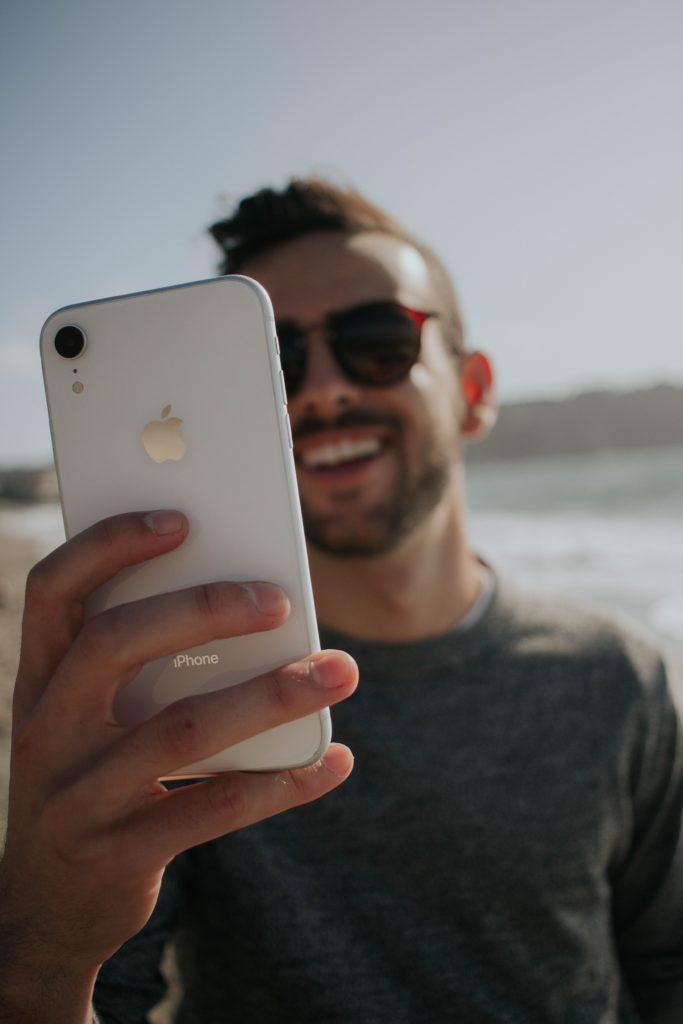 homem latino sorrindo no celular com um chip de viagem internacional