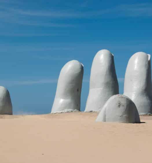 estátua cinza de dedos saindo da areia em punta del este no uruguai