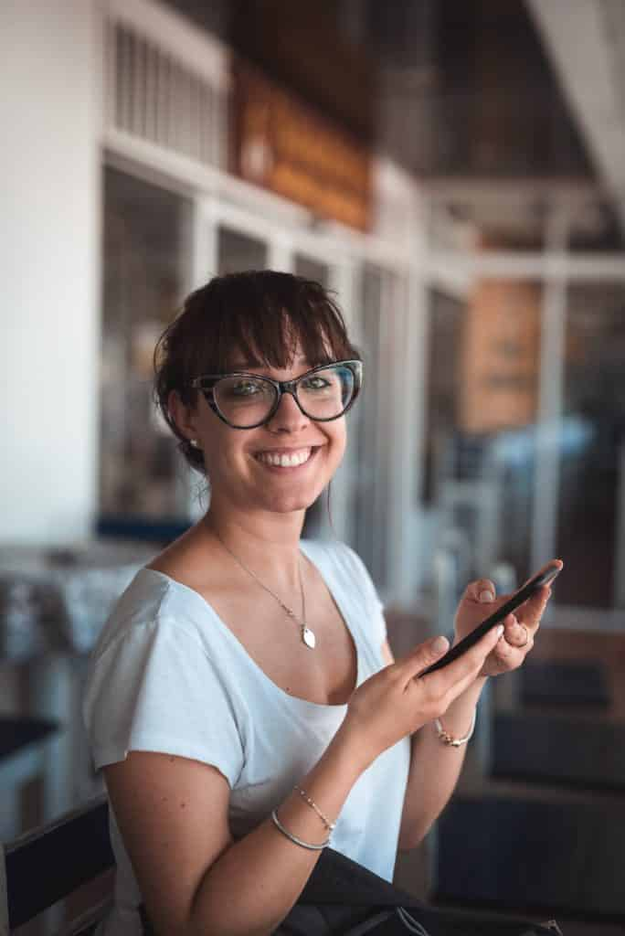 mulher sorrindo com um smartphone na mão porque tem um chip de celular para viagem internacional