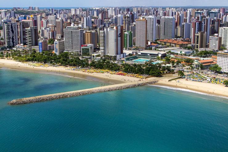 Orla do mar em Fortaleza, com diversos prédios e longa ponte