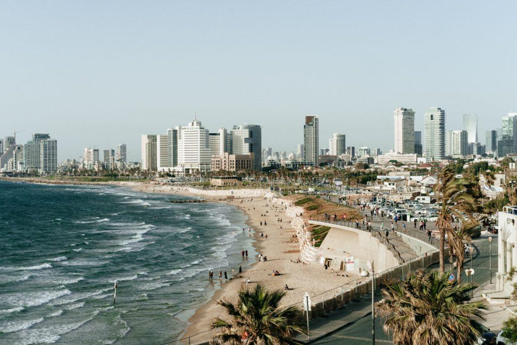 Praia com pessoas e cidade ao fundo em Tel Aviv, capital de Israel