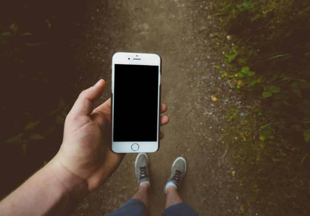 homem mexendo no celular enquanto caminha com seu chip de celular nos eua