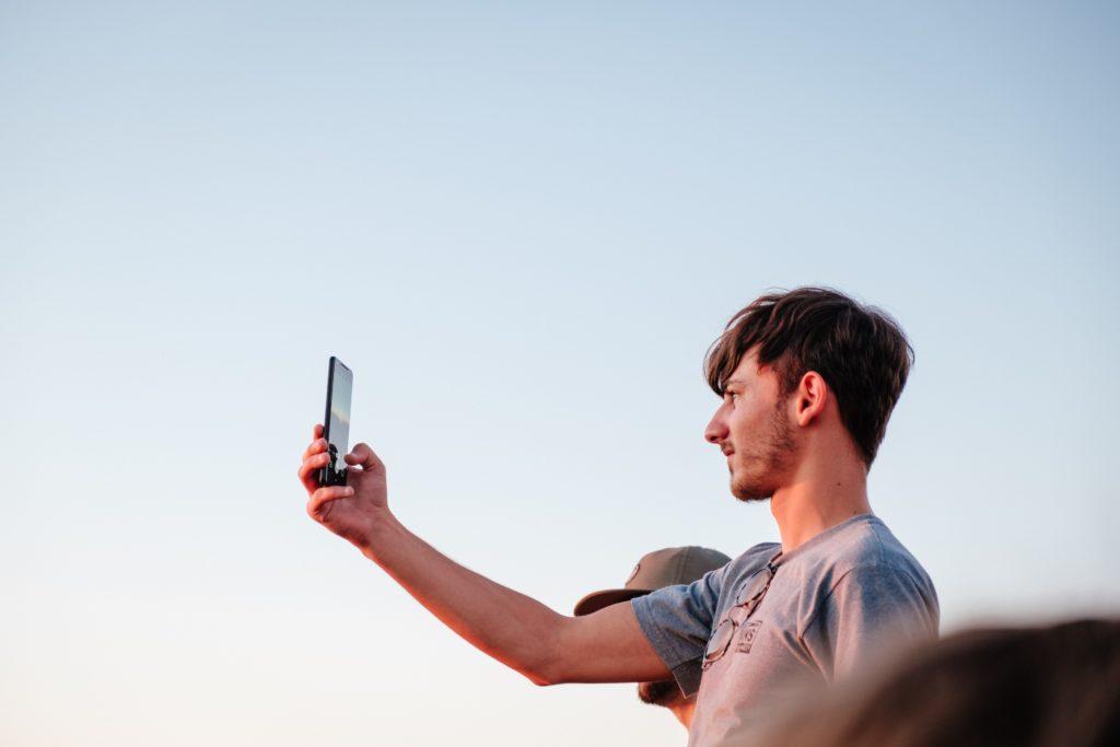 rapaz fotografando com celular a paisagem por meio do chip internacional para celular