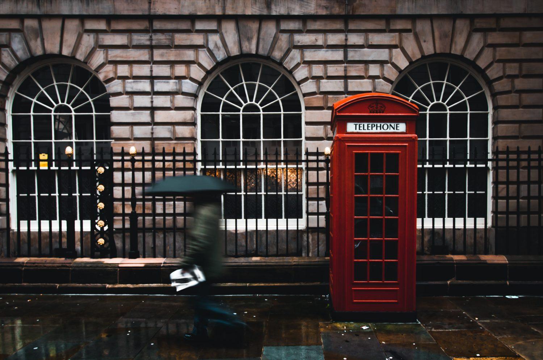 Londres em dia de chuva com pessoa andando ao lado de cabine vermelha de telefone