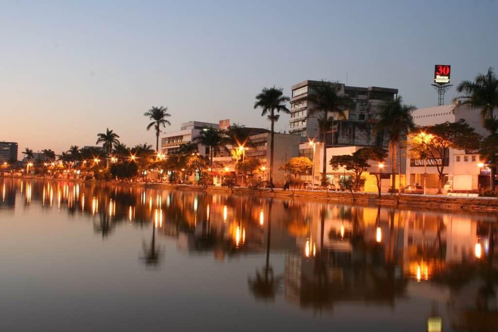 Lagoa com reflexo de árvores e prédios em Sete Lagoas, Minas Gerais