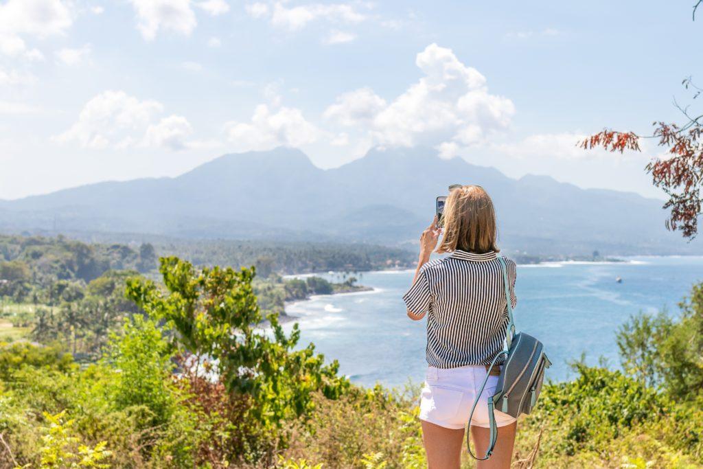 mulher fotografando a paisagem pelo iphone com um chip de celular para viagem internacional