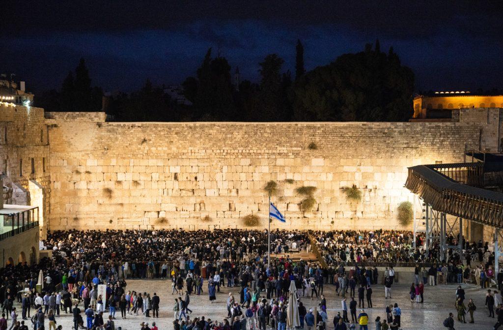 Foto do Muro das Lamentações com multidão de pessoas em frente, e pedras iluminadas durante a noite