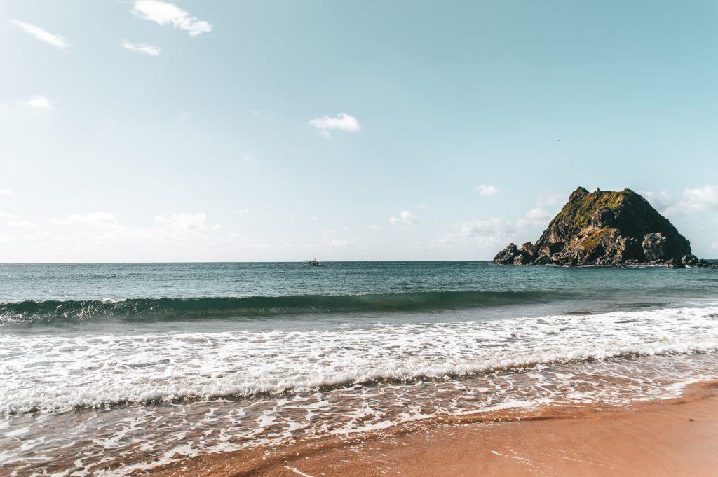 Praia da Conceição em Fernando de Noronha, com rocha no meio do mar