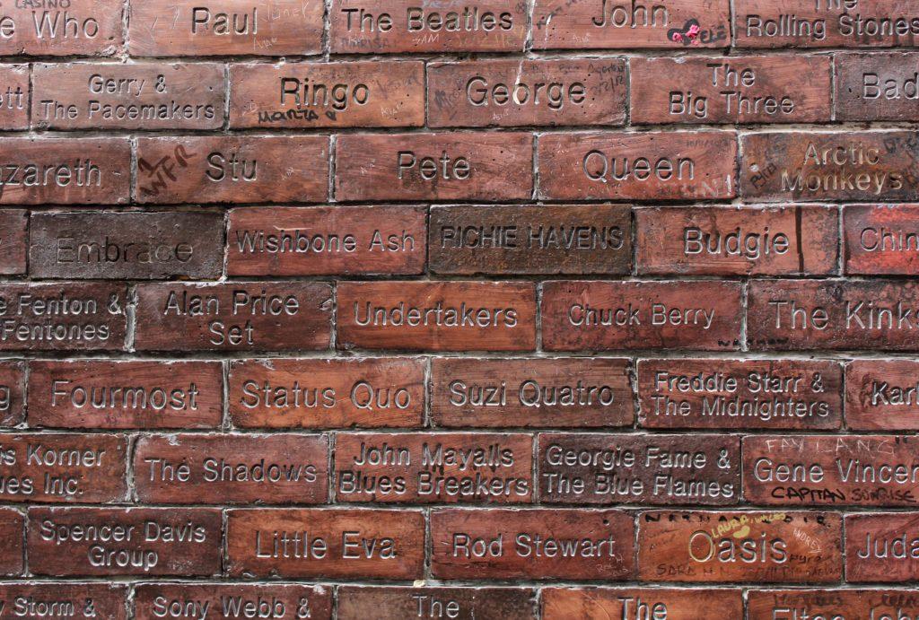 Parede de tijolos em Liverpool com nomes de bandas e cantores famosos
