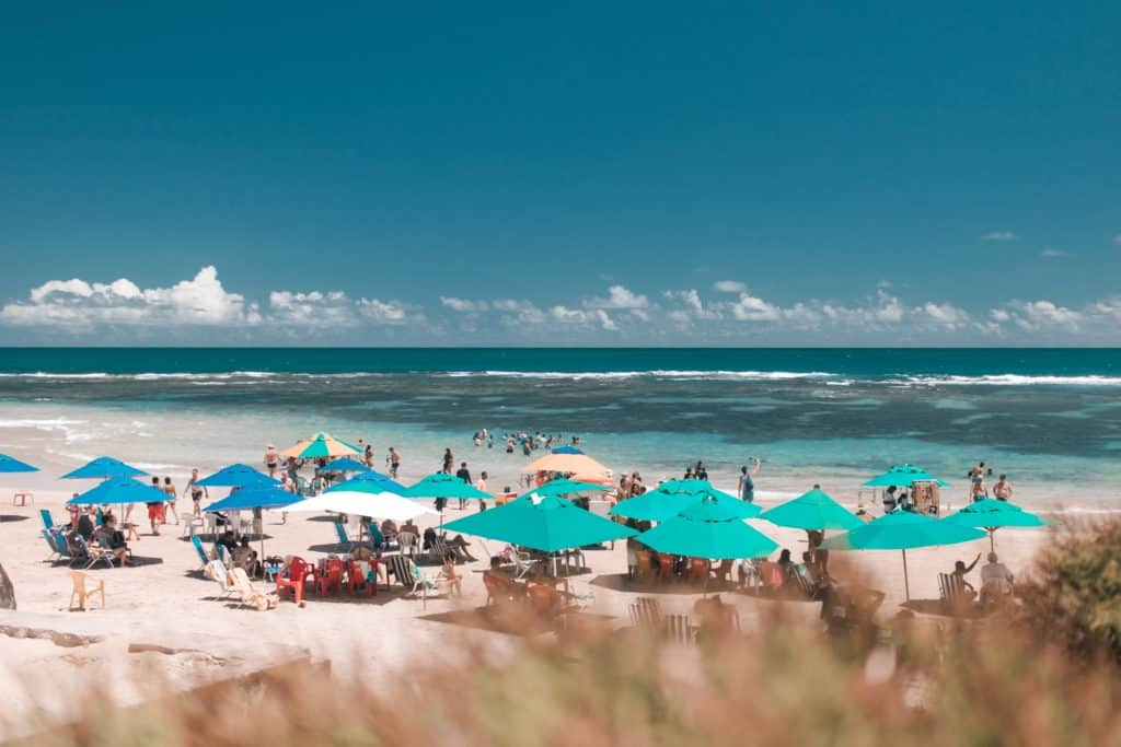 Praia com pessoas nadando e aproveitando o ambiente sob o guarda-sol