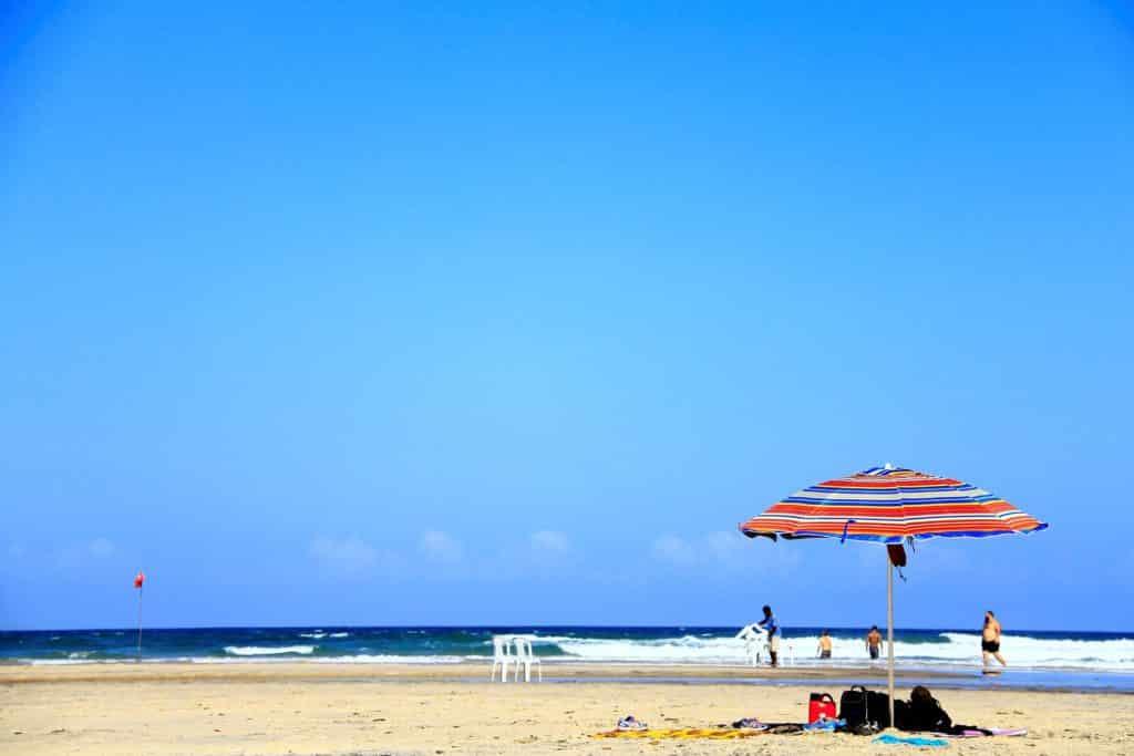 Praia Jeribucaçu em Itacaré, com guarda-sol solitário e poucas pessoas no mar