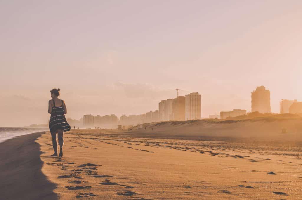 mulher caminhando a beira da praia com a cidade punta del este ao fundo