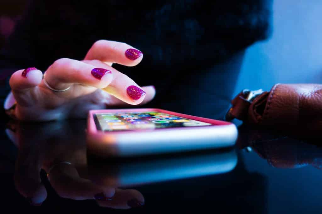 mulher digitando no celular com um chip de viagem internacional