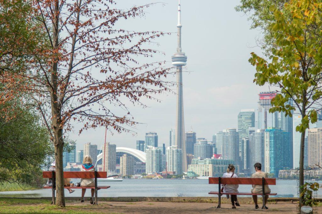 CN Tower, em segundo plano, ao lado dos demais prédios de Toronto. Em primeiro plano se vê árvores e bancos com pessoas