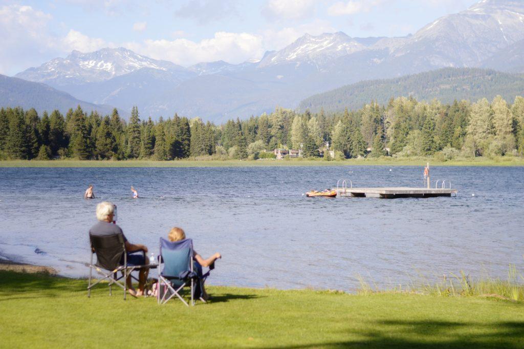 Lago em Whistler em período de tempo mais quente, com duas pessoas nadando e duas observando o lago