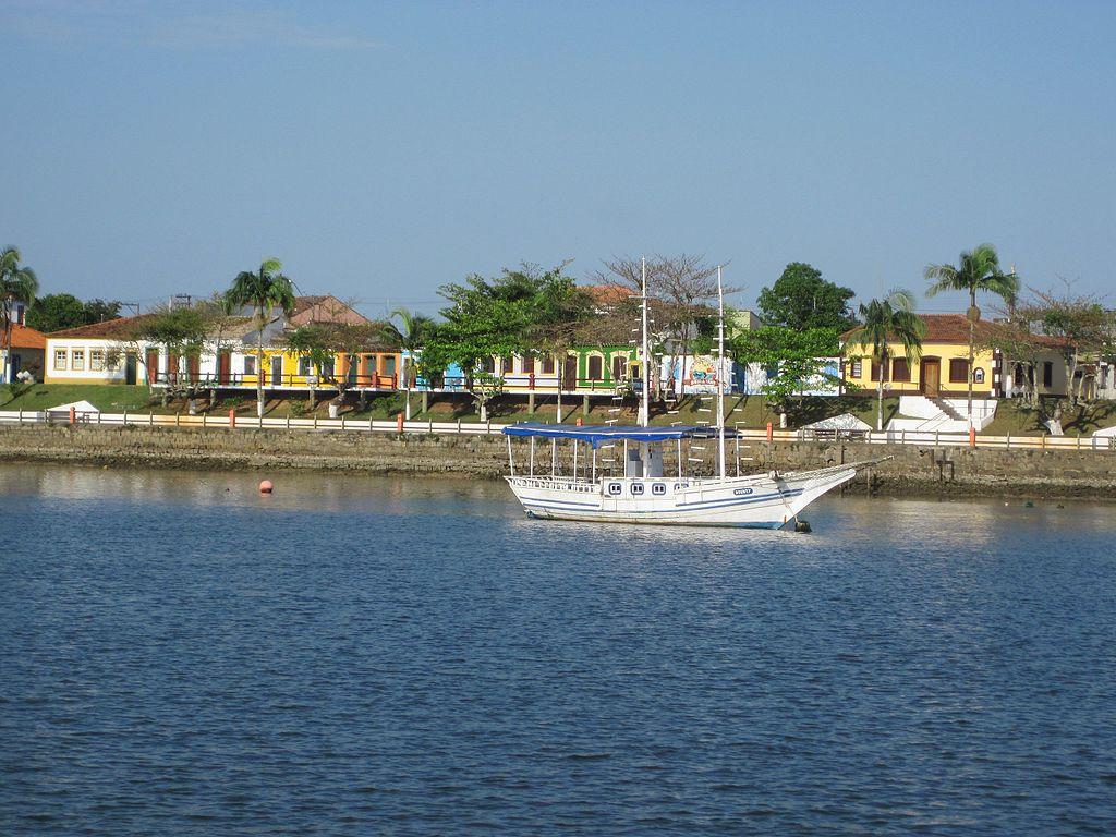 Cais no centro de Cananéia, com diversas carinhas coloridas próximas da costa e barco sobre o mar