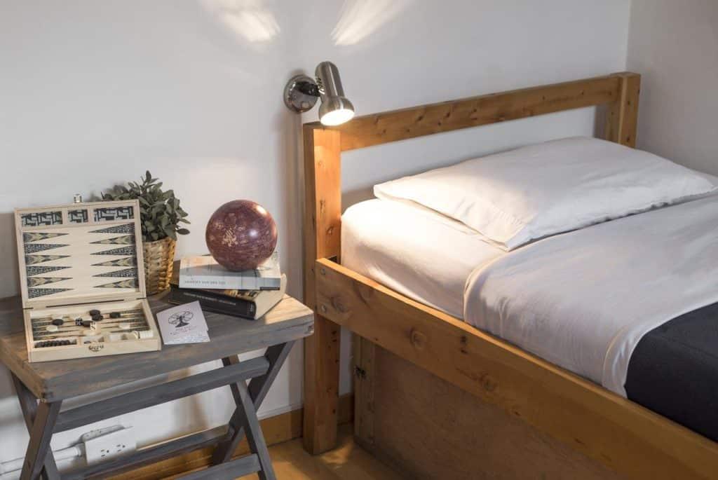 Cama e mesinha de cabeceira no Explora Hostels
