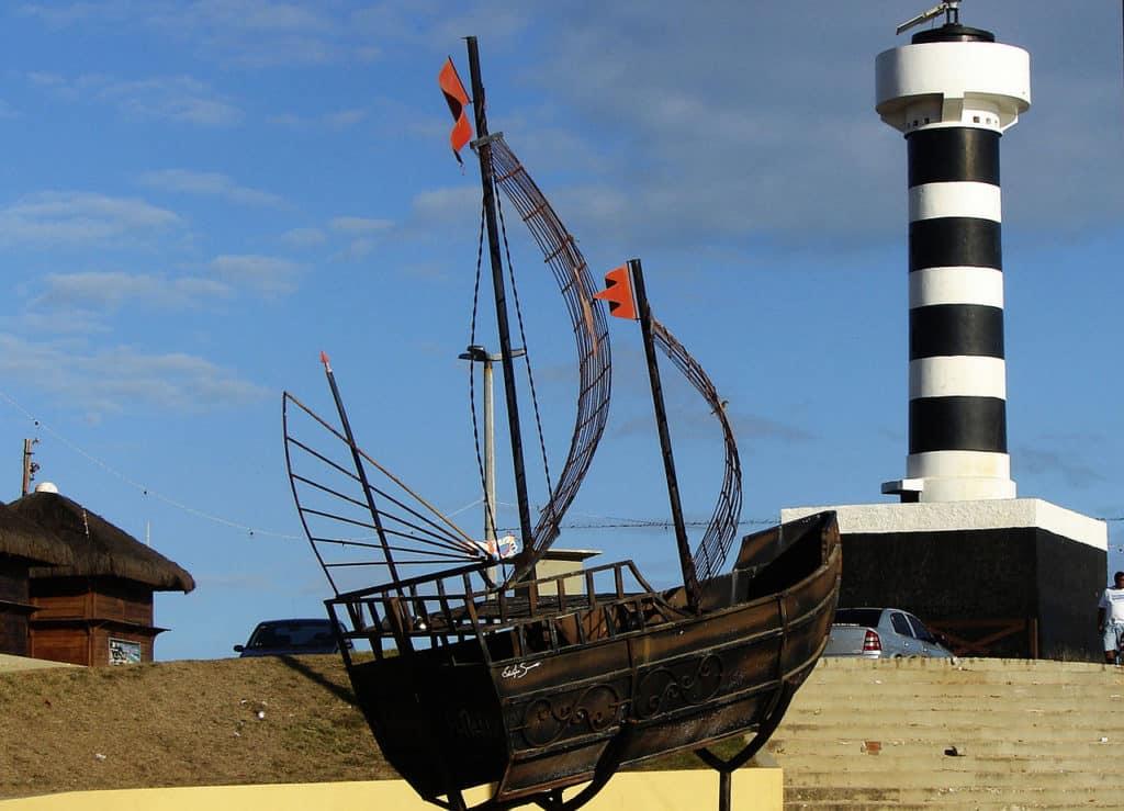 Farol de Coruripe e monumento de barco em primeiro plano