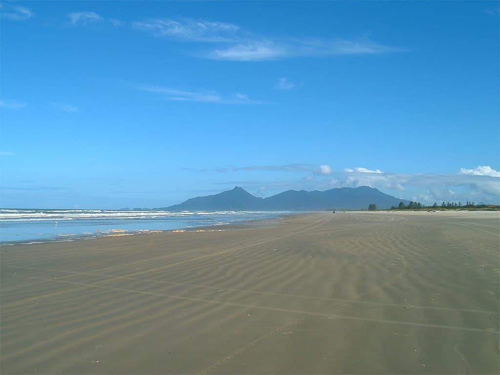 Vales de Cananéia ao fundo, em praia ampla da ilha