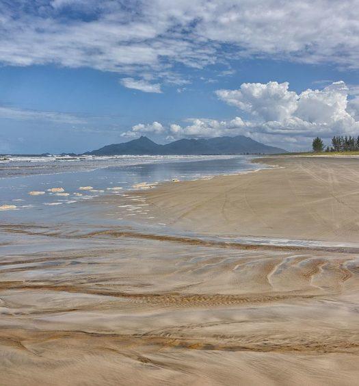 Vista de praia em Ilha Comprida, com vales do continente ao fundo