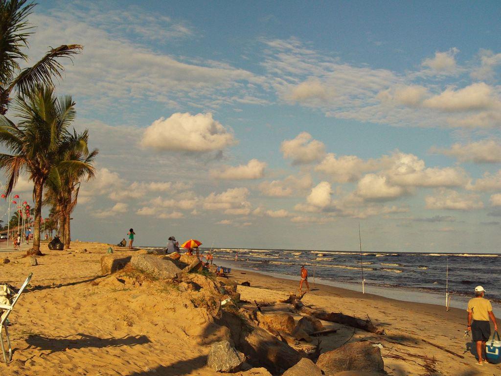 Praia em Itanhaém, com ondas baixas e pessoas circulando