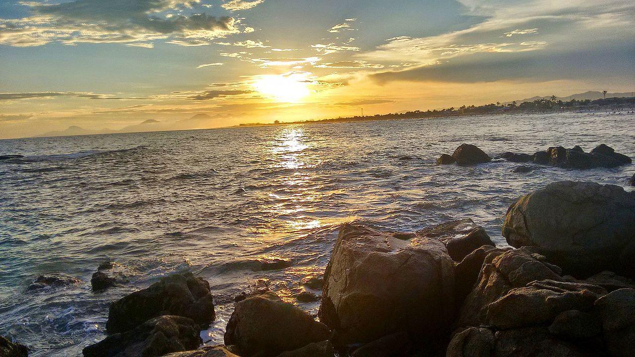 Vista de praia em Itanhaém, com rochas na beira das águas, durante o fim da tarde