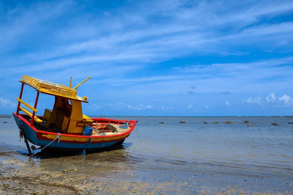 Foto de barco pequeno parado na beira da praia em Japaratinga - AL