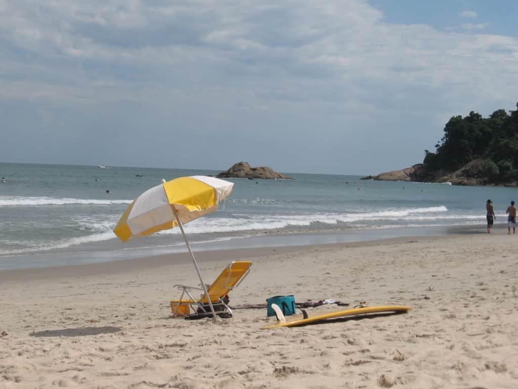 Guarda-sol, cadeira de praia, bolsa térmica e prancha na areia de Juquehy