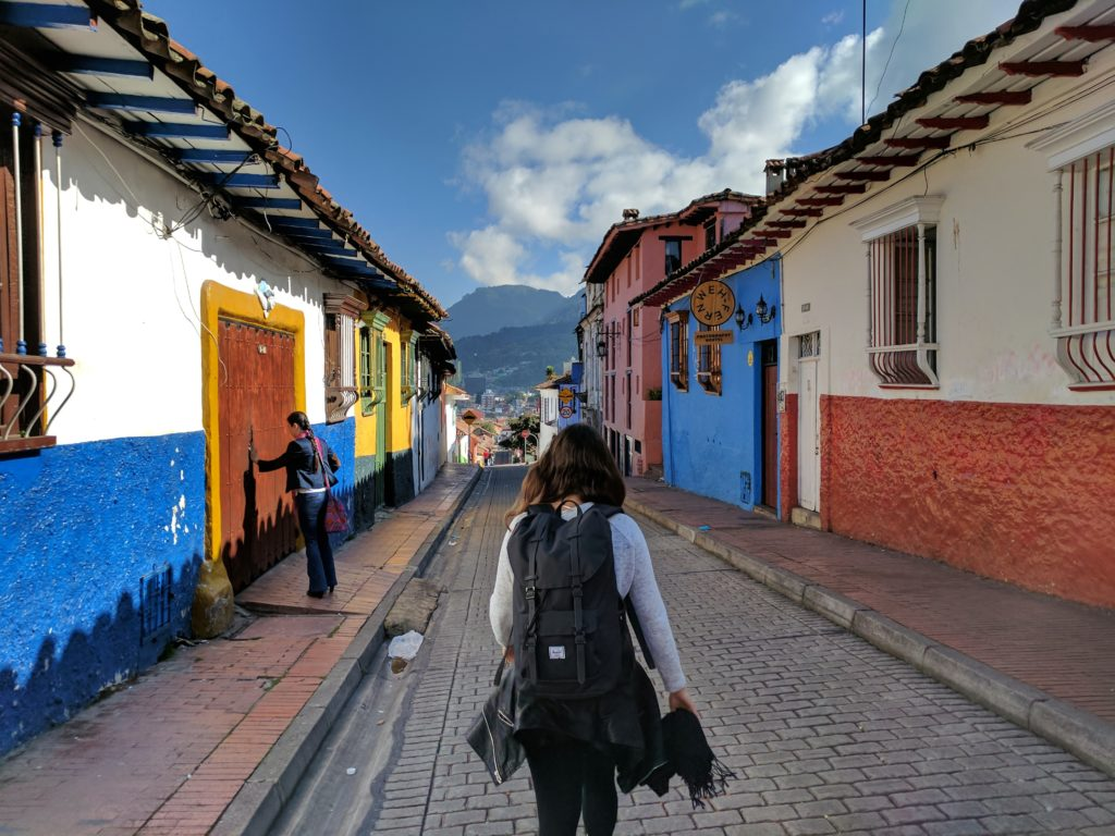 Rua estreita de paralelepípedos e casinhas coloridas no bairro La Candelária