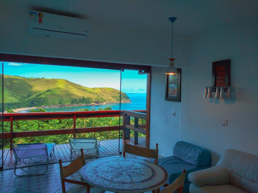 Sala do Loft Sol e Lua TTG com varanda e vista para o mar