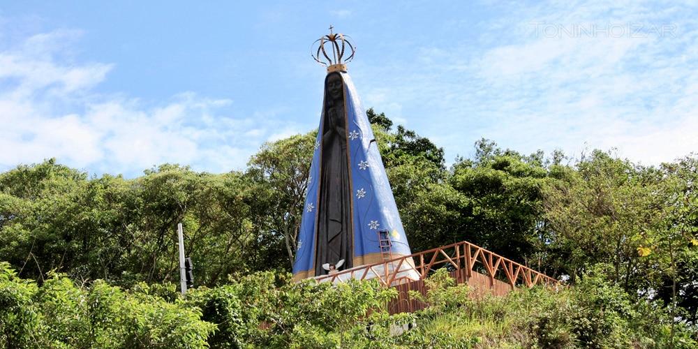 Monumento de Nossa Senhora Aparecida no Morro da Padroeira, cercada por vegetação