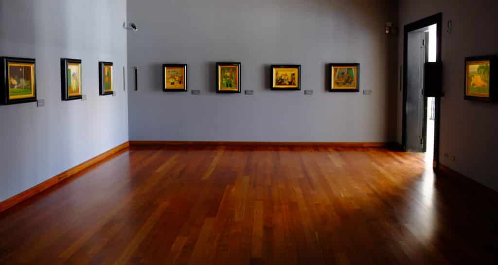 Quadros expostos em sala espaçosa de paredes azuis claras no Museu Botero