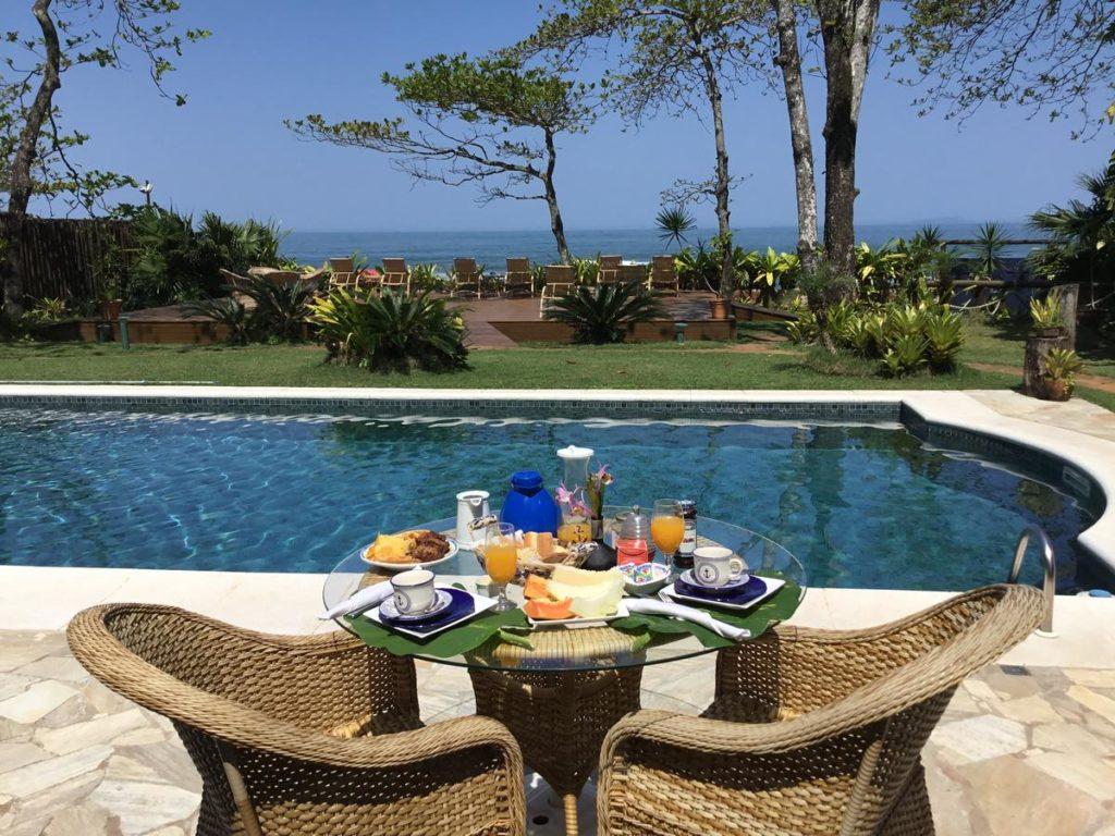 Café da manhã em mesa ao lado da piscina da pousada em Camburi Paradiso Al Mare