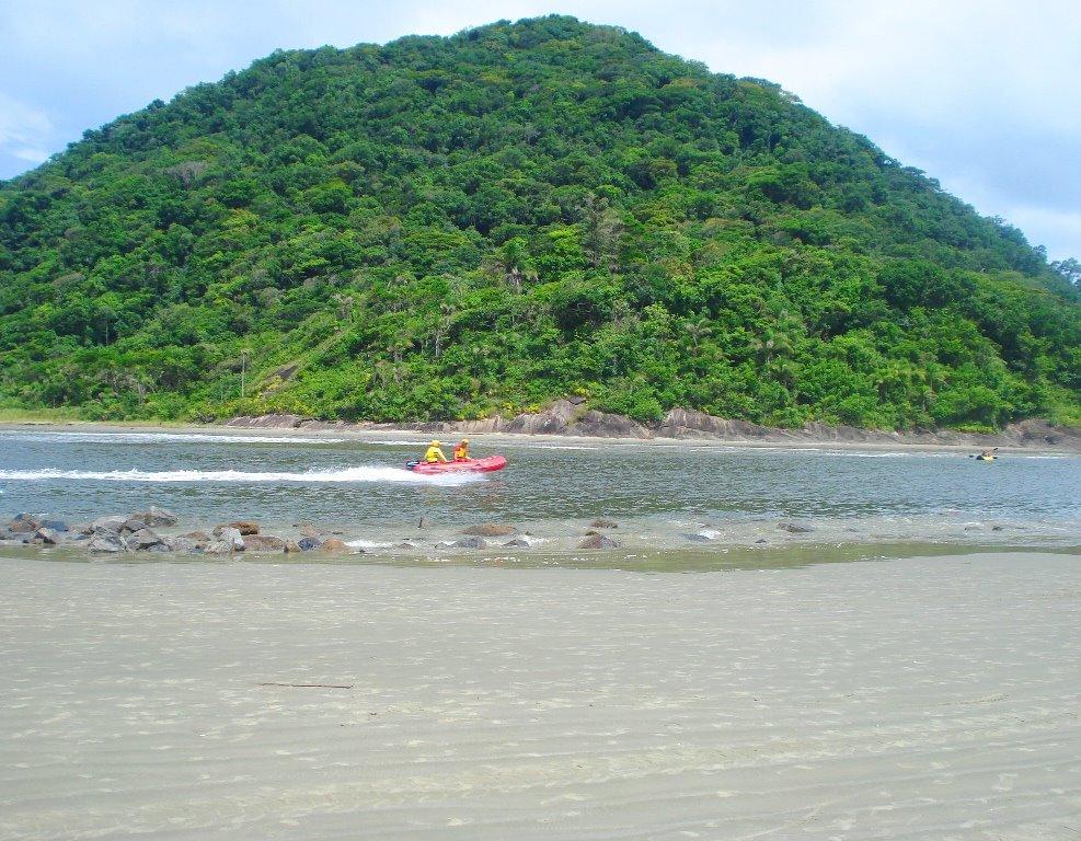 Mata em ilha, águas com pessoas passando em barco, e faixa de areia da Praia de Guaraú, em Peruíbe