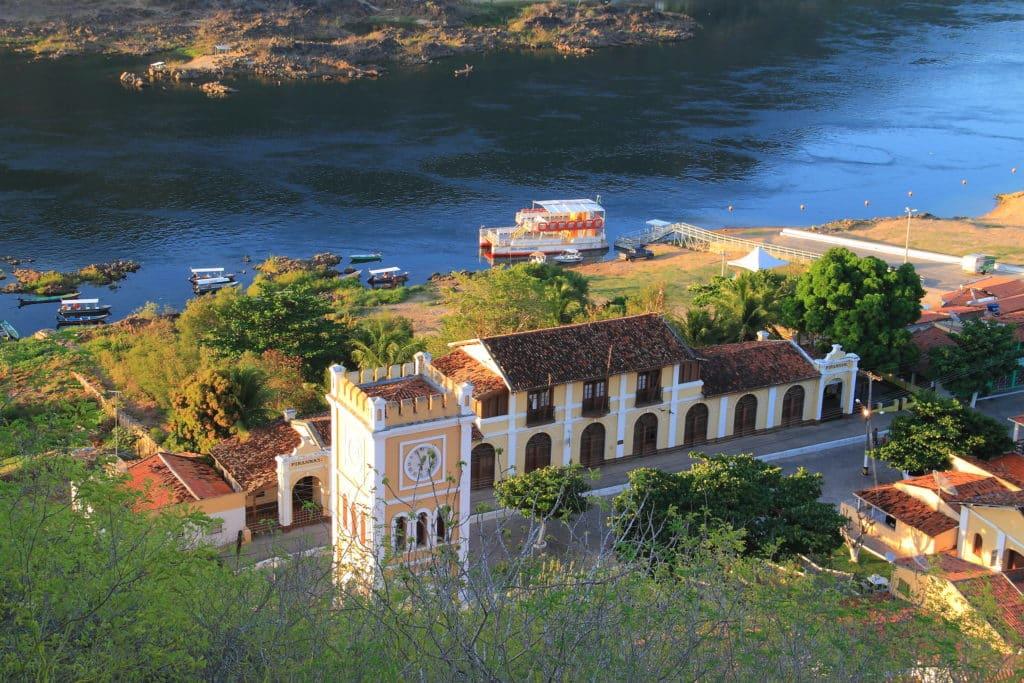 Torre do Relógio de Piranhas, com casarão antigo ao fundo e visão do Rio São Francisco