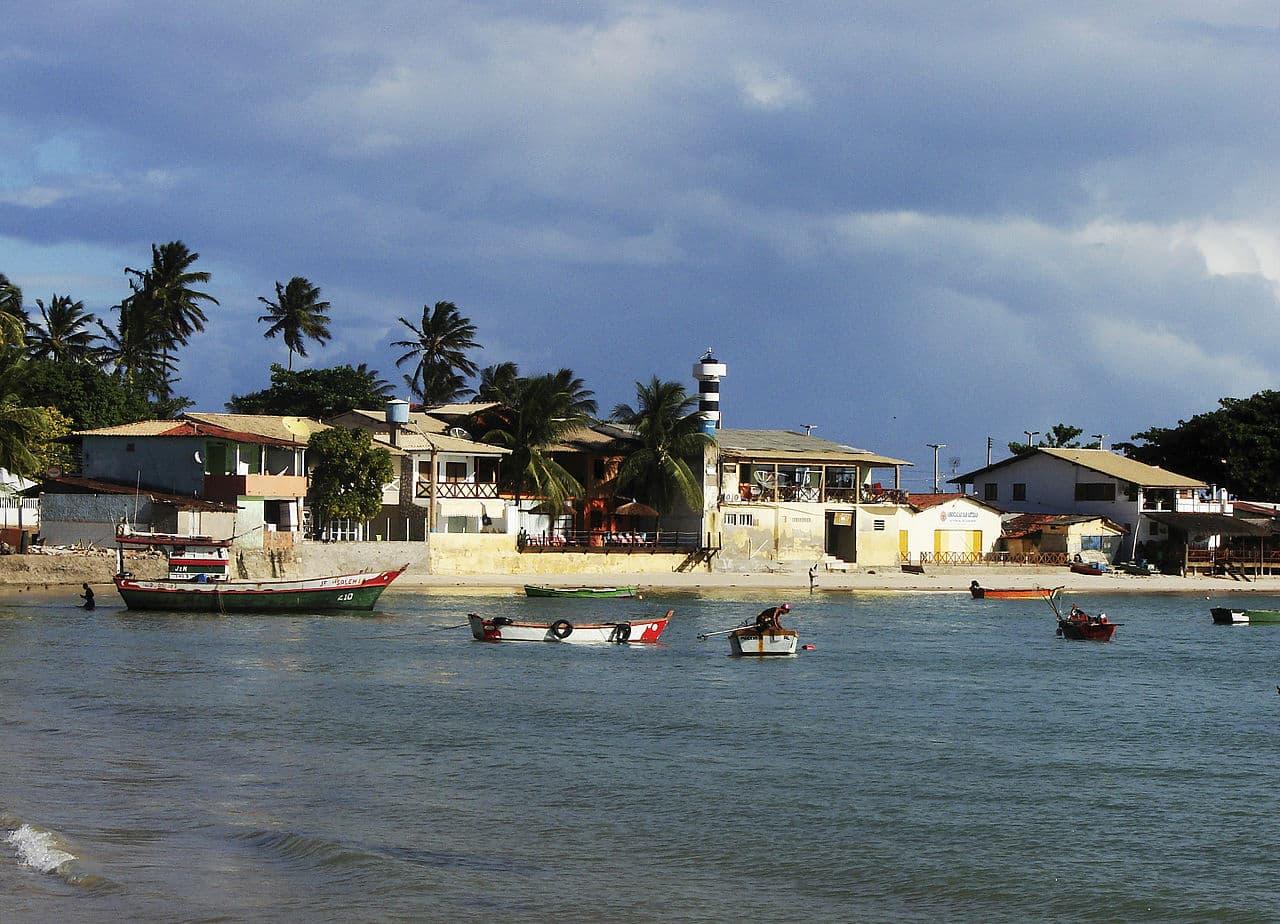 Vista do Pontal do Coruripe, com casinhas e farol próximos ao mar