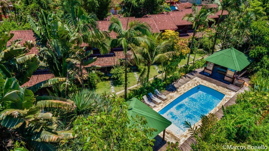 Área de piscina com bastante vegetação em volta na Pousada Portal do Cacau, uma das pousadas em Camburi
