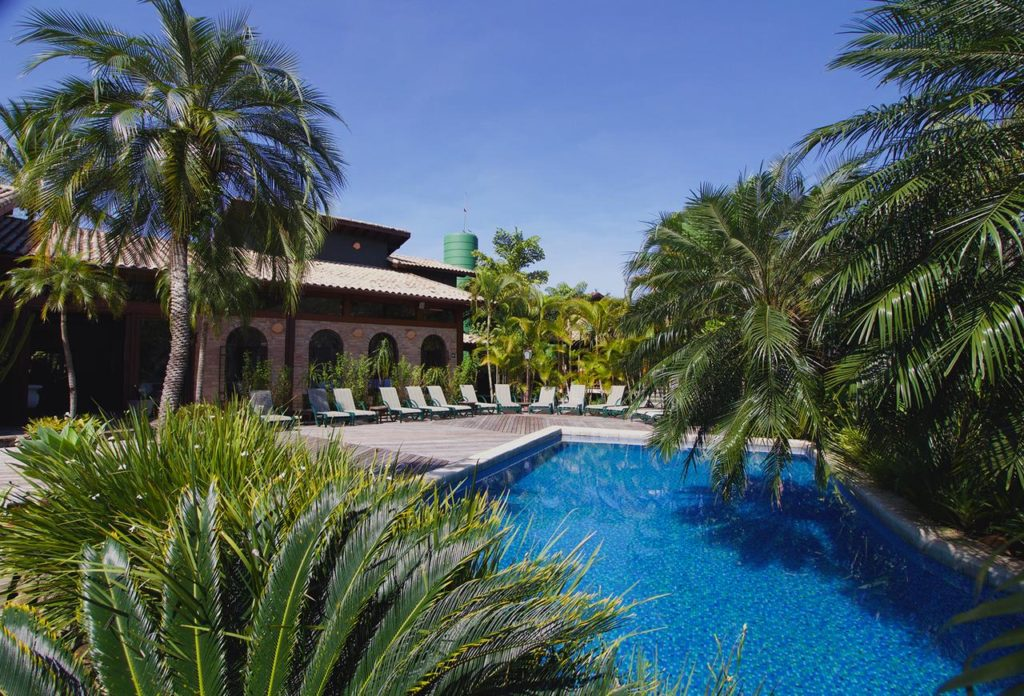 Piscina com jardim e espreguiçadeiras no Villa Babek Hotel, uma opção entre as pousadas em Camburi