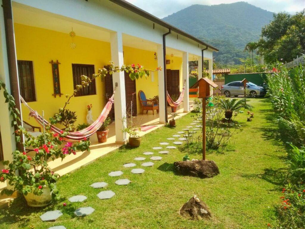 Quintal com jardim, caminho de pedras e redes na Burdul's House