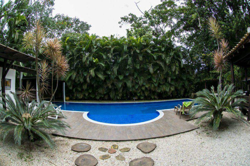 Piscina envolta por vegetação na Guest House da Lui