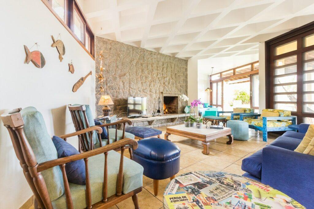Sala ampla com poltronas, sofá, TV e lareira no Airbnb Maravilhosa casa pé na areia