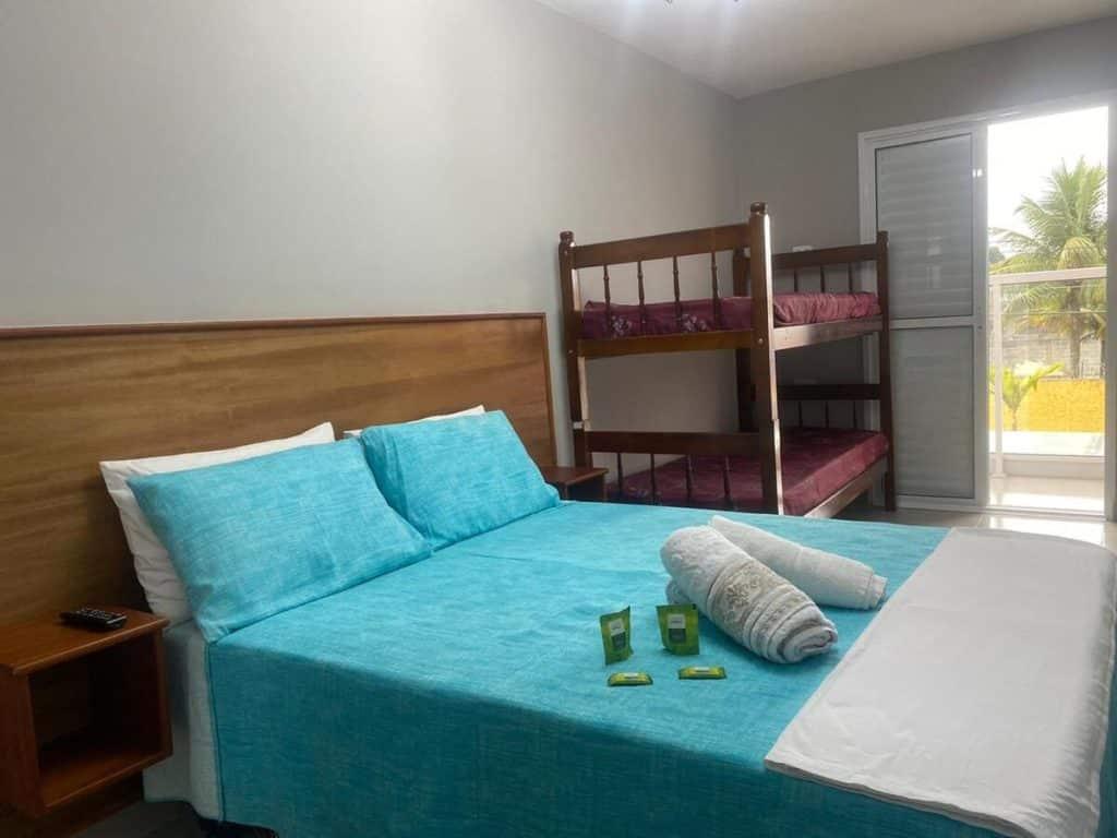 Cama confortável e beliche em quarto privativo na Pousada Praia Grande Hostel