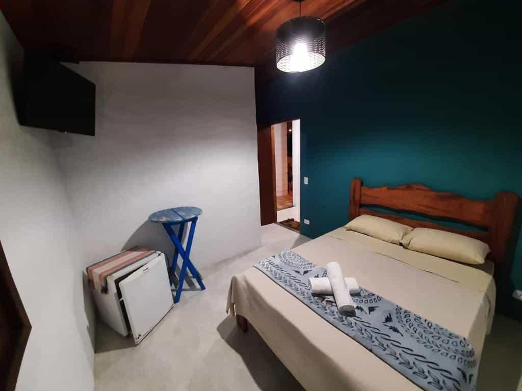 Quarto com cama ampla, frigobar e TV no Refúgio Prumirim