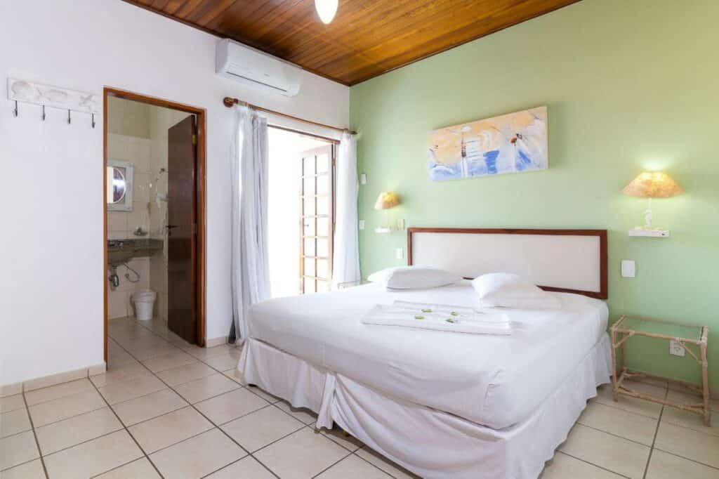 Quarto espaçoso com cama ampla na Pousada Farol do Itaguá